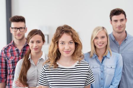 Half body shot van vijf jonge mensen uit het bedrijfsleven in casual kleding binnen het kantoor, met jonge vrouwelijke leider, bij de Camera glimlacht Stockfoto