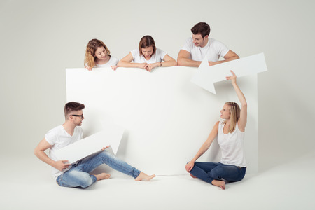 denim jeans: Young Best Friends in Casual Clothing, Holding White Large Board and Arrows with Copy Space Against Off-White Background.