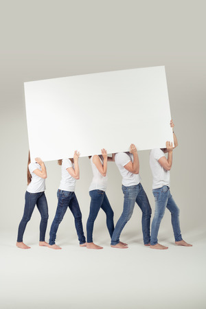 empty of people: Group of People in Casual Outfits Carrying Empty White Large Board Over their Shoulders, Emphasizing Copy Space. Captured in Studio.