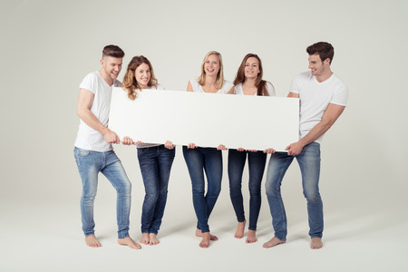 a placard: Group of Cheerful Young Friends Holding Blank White Board with Text Space Together on Off-White Background.