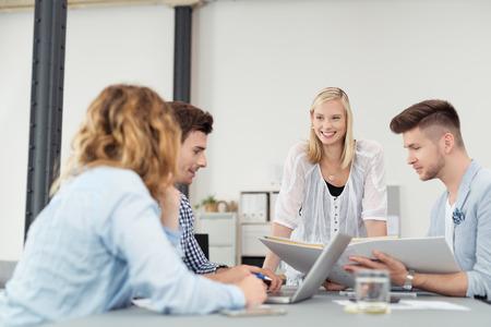 jovenes felices: Mujer Alegre Tomar el plomo a un Encuentro Empresarial para Jóvenes Profesionales Dentro de la sala de juntas Foto de archivo