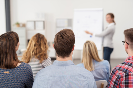 speaking: Rear View of Young Office Workers in Casual Outfits Listening to a Top Manager Explaining Something Using Illustrations. Stock Photo