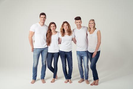 흰색 배경에 대해 미소를 카메라 캐주얼 평범한 흰색 셔츠와 청바지에 행복 젊은 친구의 그룹입니다.