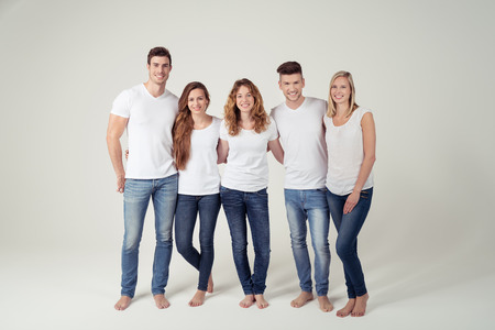 to white: Group of Happy Young Friends in Casual Plain White Shirts and Blue Jeans Smiling at the Camera Against White Background.