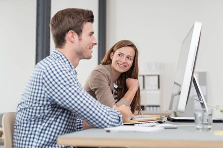 empleado de oficina: Smiling Pretty Office Worker Admiring her Handsome Colleague While Working at his Desk.