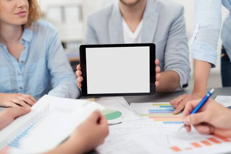 emphasizing: Businessman in a Meeting at the the Boardroom, Showing an Empty Screen of a Tablet Computer, Emphasizing Copy Space.