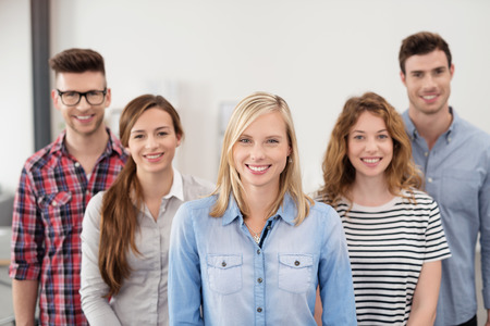 La mitad Shot Cuerpo de cinco jóvenes profesionales Oficinistas vistiendo ropa casual sonríe en la cámara. Foto de archivo