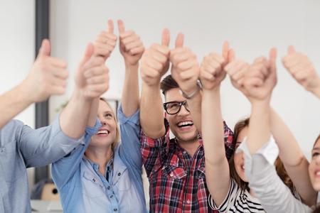 Squadra di giovani felici mostra i pollici in segni mano alta insieme all'interno dell'Ufficio. Archivio Fotografico