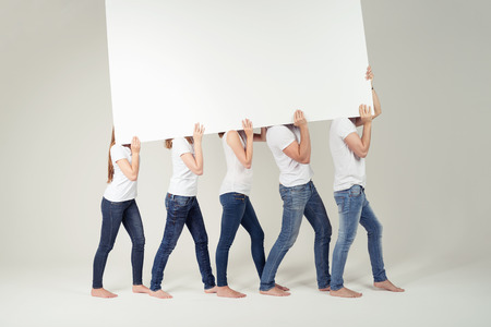 jean: Group of Friends in Casual Shirts and Jeans Carrying Empty White Large Board Ready for Advertisement Together Over their Shoulders. Captured in Studio.