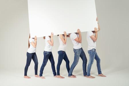 Grupo de amigos en las camisas sport y pantalones vaqueros que llevan vacío Large White Junta Listo para Publicidad juntos sobre sus hombros. Capturado en Studio.