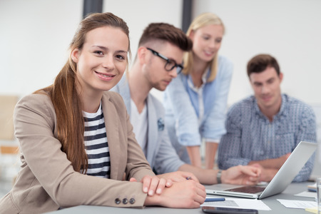 students group: Pretty Young Office Worker in a Meeting at the Boardroom, Looking at the Camera with a Smiling Face.