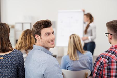 Giovane Ragazzo in una riunione di lavoro sorride alla macchina fotografica dalla sua schiena mentre qualcuno sta Spiegando.