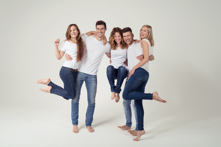 Team of Five Happy Young People Posing Funny in Casual White Shirt and Blue Jeans Outfits on White Background Inside the Studio.