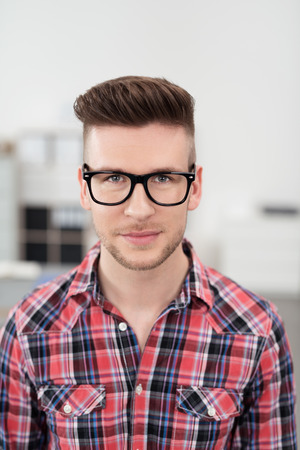 nerd: Portrait of a Handsome Young Man In the Office, Wearing Checkered Shirt with Eyeglasses, Looking at the Camera.
