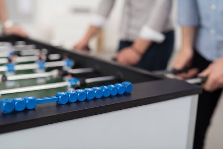rolled up sleeves: Mid section of two people wearing shirts with rolled up sleeves playing foosball, focus on foreground Stock Photo