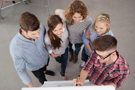 Veduta dall'alto di un Team Leader maschio Presenta Qualcosa su un poster per il Gruppo all'interno dell'ufficio. Archivio Fotografico - 42556103