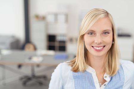 매력적인 이빨 미소와 함께 카메라를 찾고, 금발 머리와 함께 꽤 젊은 사무실 여자를 닫습니다.