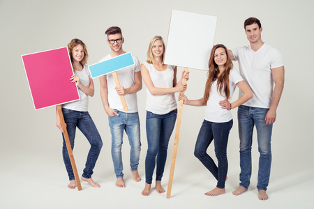empty of people: Smiling Young Friends in Casual Clothing, Holding Empty Colored Placard with Copy Space on Off White Background Inside the Studio.