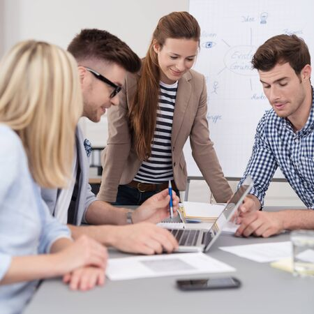 casual clothing: Four Young Business People in Casual Clothing, Looking at the Document Together While Having a Corporate Meeting Inside Boardroom