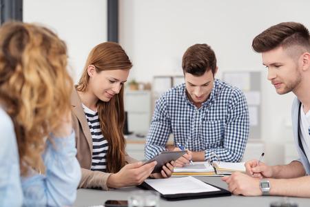 オフィス内のテーブルでのビジネス会議を持っているカジュアル衣料に 4 名のプロ若者