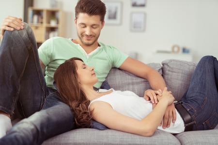 novio: Bastante Novia joven que miente en el regazo de su novio guapo mientras se relaja en el sofá de la sala de estar. Foto de archivo