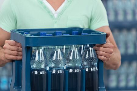 carry: Close up Man Holding One Dozen of Bottled Water with No Label in a Blue Plastic Case.