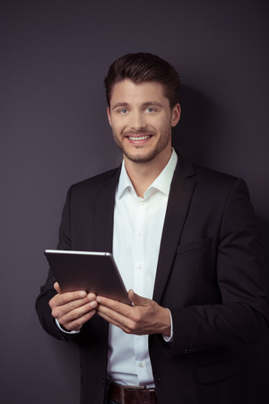 smiling businessman: Portrait of a Handsome Young Businessman Holding his Tablet Computer, Smiling at the Camera Against Gray Wall Background.