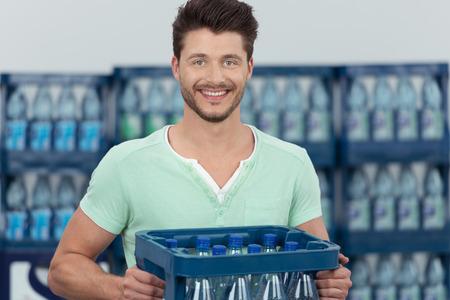 carry: Close up Smiling Handsome Young Bearded Guy Carrying a Case of Bottled Water and Looking at the Camera.