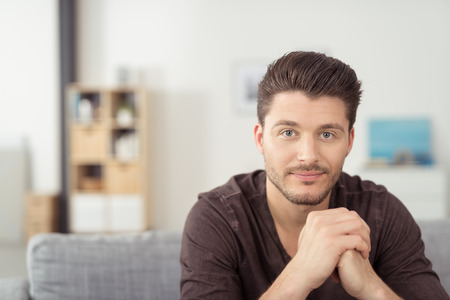 male       hand: Portrait of a Gorgeous Young Bearded Guy Sitting on the Couch at the Living Room and Staring at the Camera Stock Photo