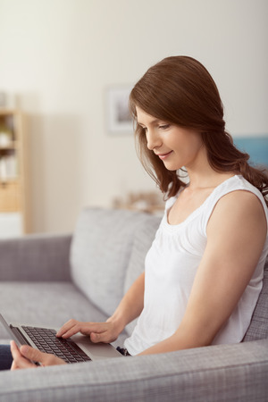 Pretty Young Woman Using her Laptop Computer While Relaxing at the Couch in the Living Room.