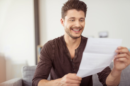 person reading: Close up Good Looking Young Bearded Guy Reading a Letter at the Couch with a Happy Facial Expression Stock Photo