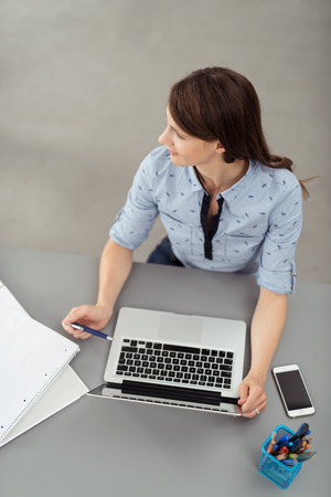 work table: High Angle View of a Young Office Woman Sitting at her Desk with Laptop Computer, Looking Into Distance. Stock Photo