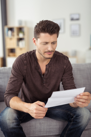 domiciles: Close up Handsome Young Man in Casual Clothing, Reading a Letter Seriously While Sitting at the Couch In the Living Room.