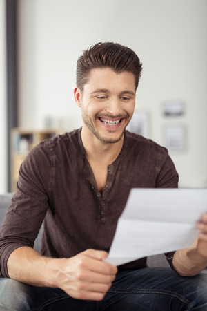 one sheet: Close up Cheerful Handsome Young Guy Sitting at the Couch, Laughing While Reading a Letter from a Friend Stock Photo