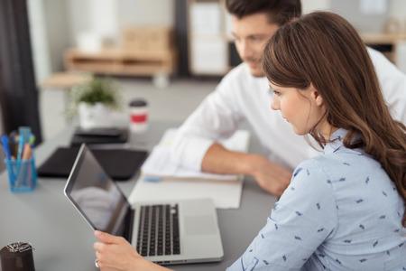 그녀의 책상에서 그녀의 남성 동료와 진지하게 그녀의 노트북 컴퓨터에 뭔가보고 젊은 사무실 여자.