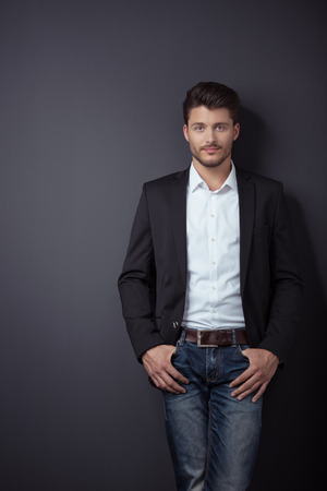 cool man: Portrait of a Handsome Young Businessman Leaning Against Gray Wall Background with Copy Space and Looking at the Camera.