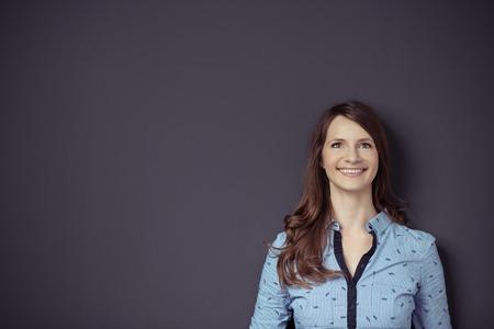mujer sola: Muchacha bonita que mira para arriba con feliz expresión facial contra el fondo gris de la pared con espacio de la copia en la izquierda.