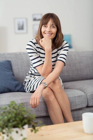 piernas mujer: Retrato de una mujer feliz que se sienta en el sofá con las piernas cruzadas y la mano en su barbilla, mirando a la cámara Foto de archivo