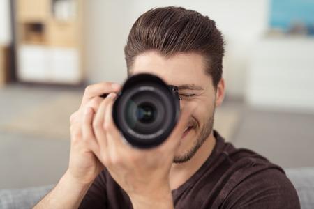 카메라에 직면 동안 DSLR을 사용하여 사진을 촬영 행복 좋은 찾고 젊은 남성 작가를 닫습니다.