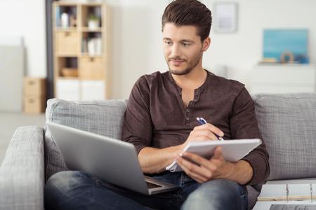 hombre escribiendo: Hombre joven hermoso que se sienta en la sala de estar sofá, escribiendo algunas notas mientras busca a su ordenador portátil Foto de archivo