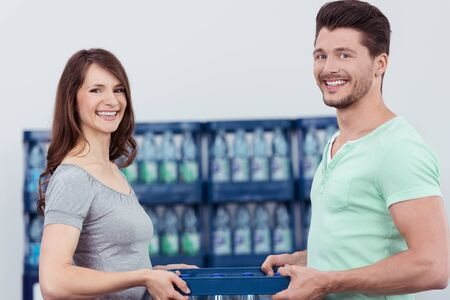 carry: Happy Young Lovers Holding a Case of Bottled Water Together Inside the Department Store, Looking at the Camera with Toothy Smiles. Stock Photo