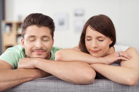 ojos cerrados: Cierre para arriba Pareja joven que se sienta en el sofá de la sala de estar, que se inclina en sus brazos con los ojos cerrados.