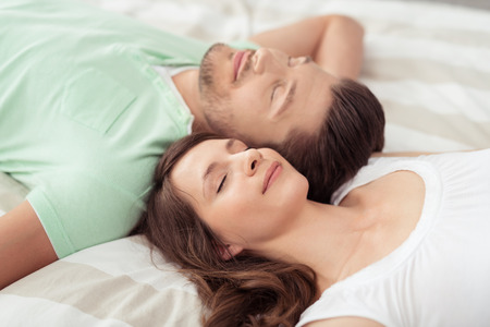 close in: Close up Young Romantic Couple Resting on White Bed with Eyes Closed in Opposite Directions During Their Day Offs. Stock Photo