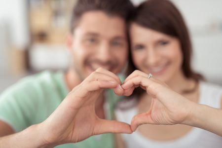 Sweet Young Lovers Making Heart Shape using Bare Hands in Close up at Home.