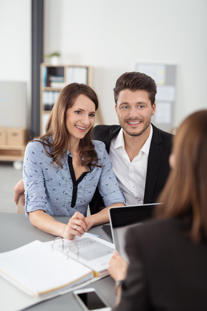 mortgage document: Sweet Happy Young Professional Couple Having a Meeting with a Financial Agent for Investments Inside the Office.