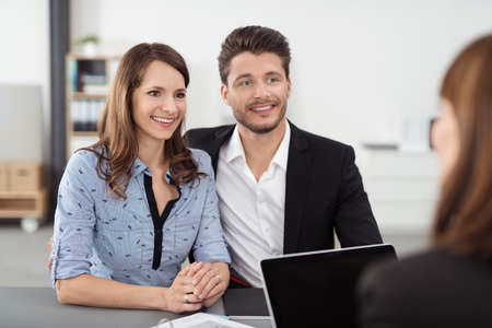 couple talking: Happy Young Professional Couple Talking to a Real Estate Agent Inside the Office Stock Photo