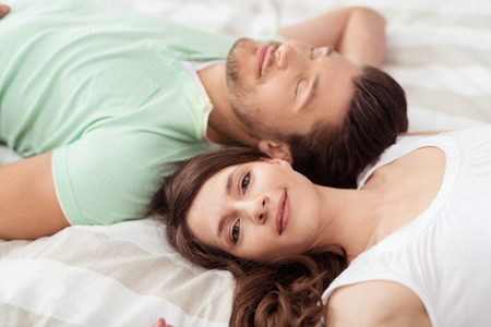 close in: Close up Pretty Woman Smiling at the Camera While Lying on Bed Beside her Handsome Boyfriend in Opposite Direction. Stock Photo