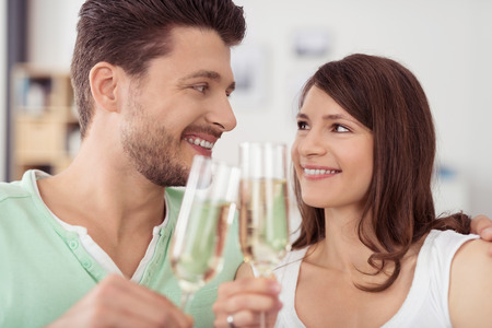 toothy smiles: Close up Sweet Young Couple Holding Glasses of Champagne Wine, Looking Each Other with Toothy Smiles. Stock Photo