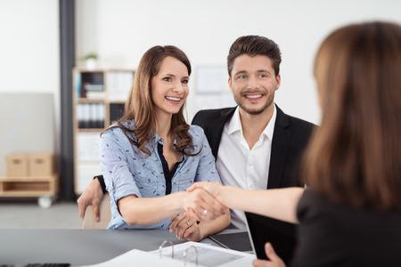 사무실 내부 일부 비즈니스 토론 후 부동산 에이전트 손을 흔들면서 행복 젊은 전문 커플.