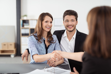 Happy Young Professional Couple Shaking Hands with a Real Estate Agent After Some Business Discussions Inside the Office. Archivio Fotografico